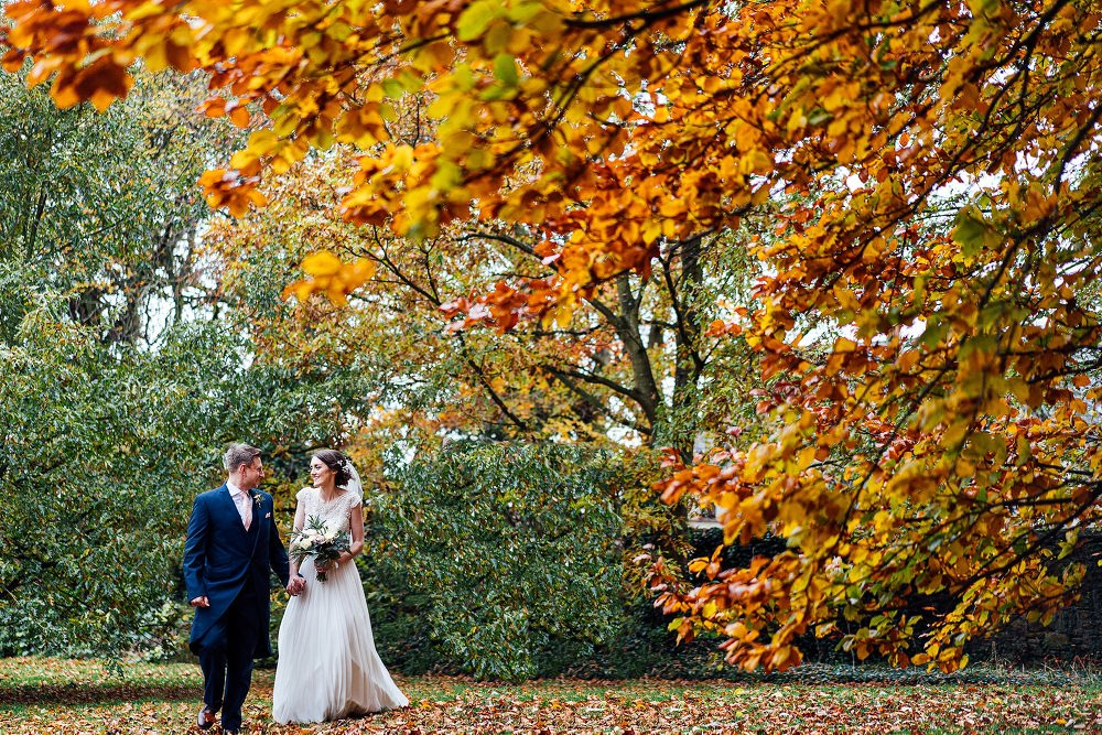 Bride & Groom walking in grounds at West Tower with orange leaves on the trees at their autumn wedding