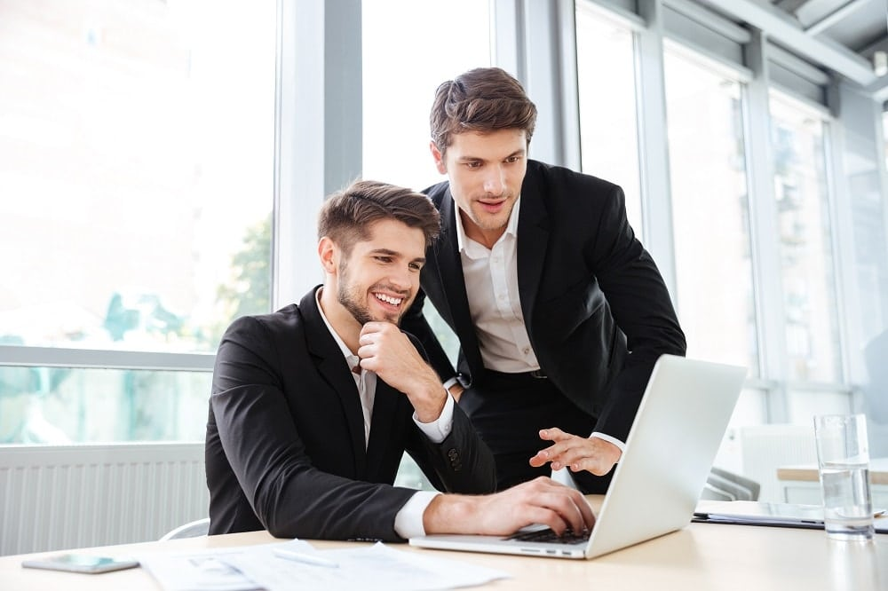two-cheerful-young-businessmen-using-laptop