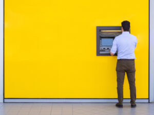 man withdrawing money from pension cash machine