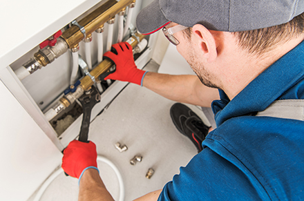 Plumbing System Fix Job. Caucasian Technician Looking For Potential Issue Inside Residential Central Heating System.