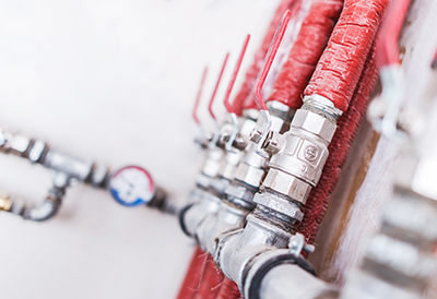 Home Plumbing System Closeup Photo. Red Isolated Pipes with Ball Valves. Residential Water Supply System.