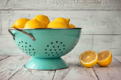 Fresh lemons in blue colander. Wooden background