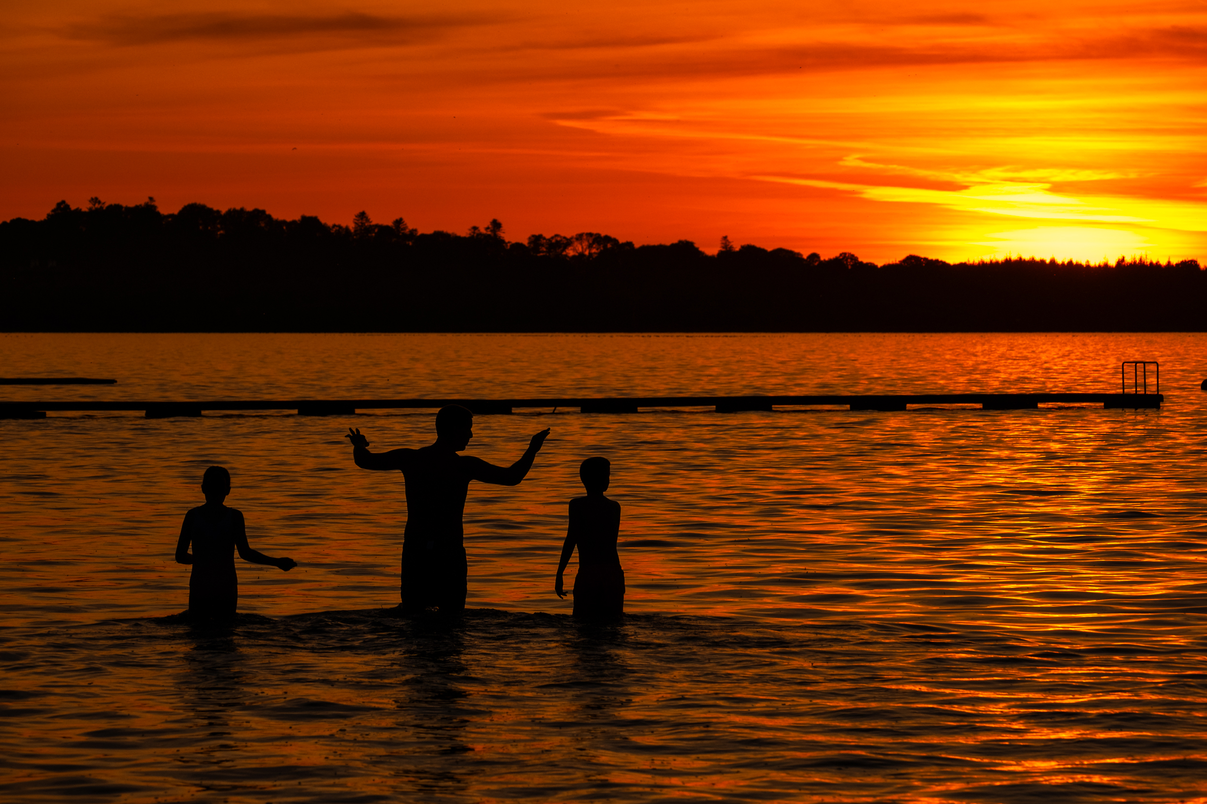 Silhouetted people playing in water at sunset