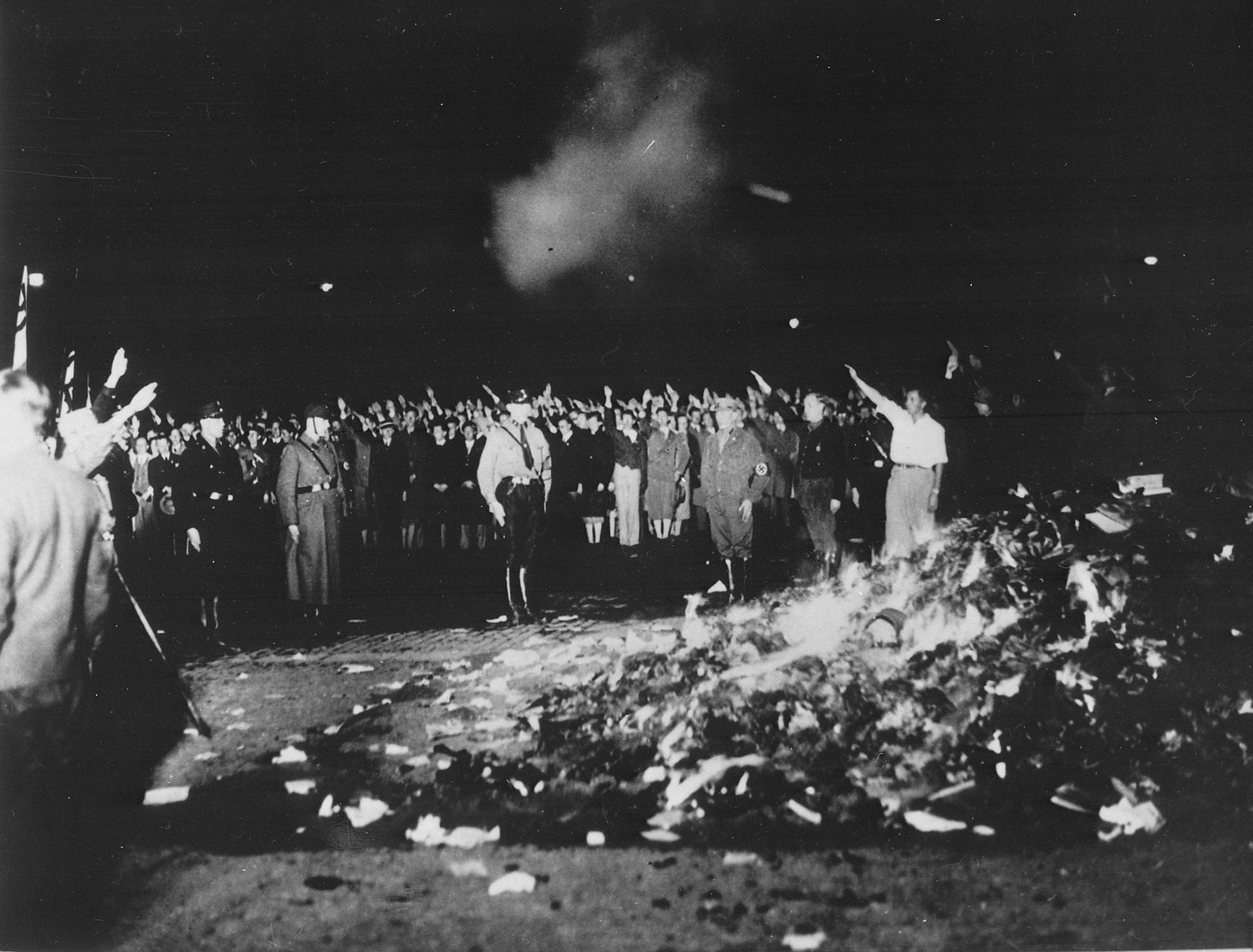 Thousands of books smoulder in a huge bonfire as Germans give the Nazi salute during the wave of book-burnings that spread throughout Germany