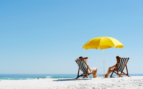 Sandy beach with two people sat on deckchairs beneath a parasol
