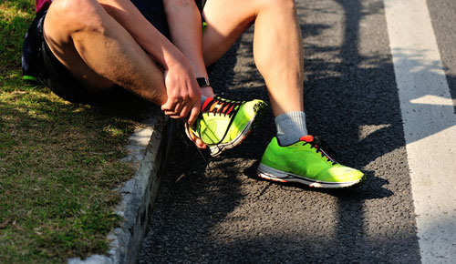 Runner clutching an injured ankle on a kerb