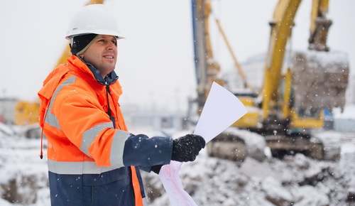Man working on site during winter with heavy plant