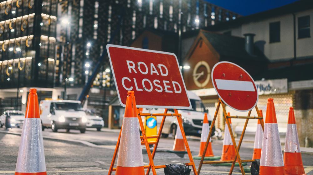 Inner city road closed by orange roadblock cones during night maintenance