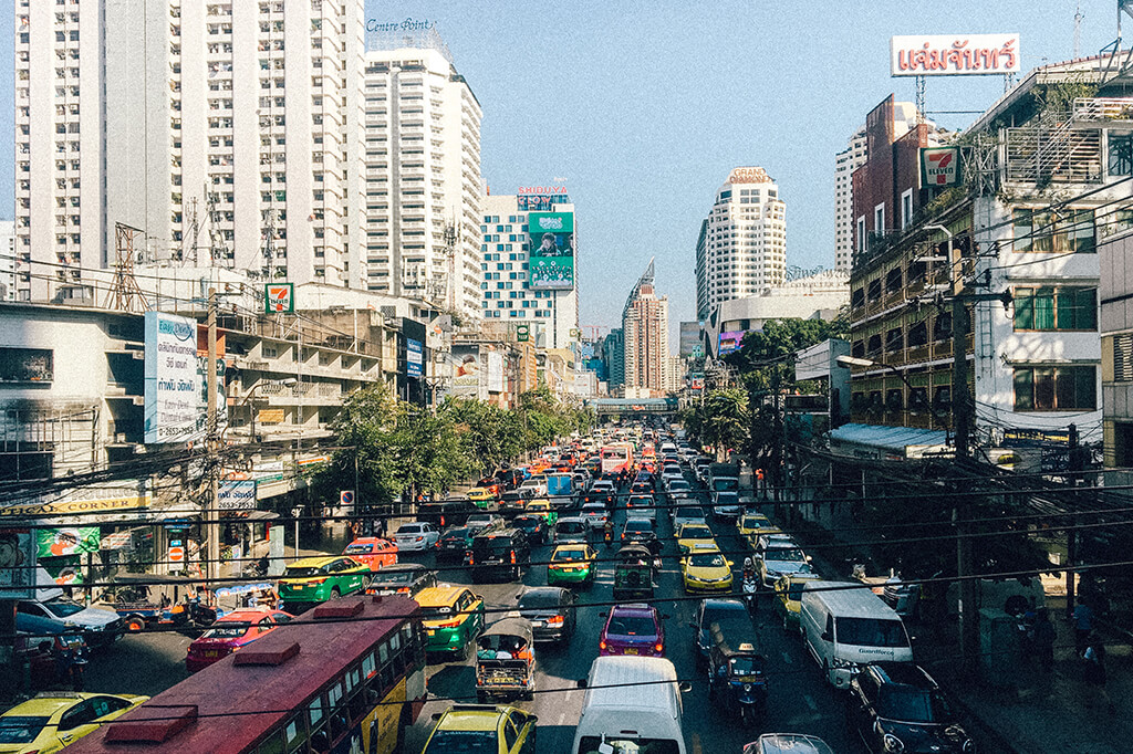 A view of a busy thai street full of cars.