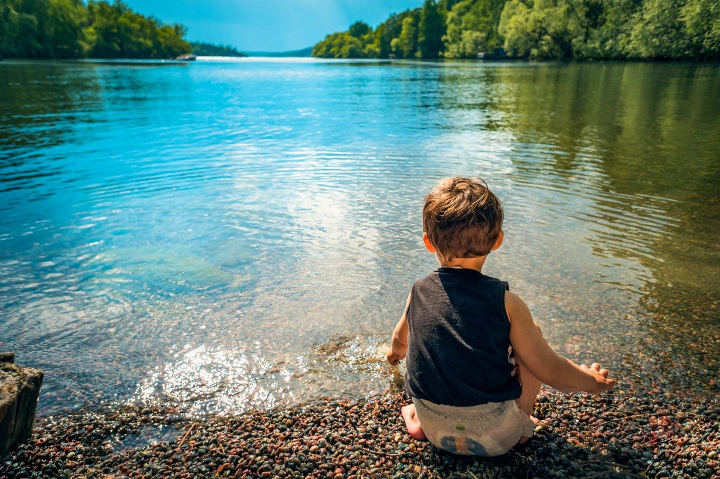 toddler sitting by open water