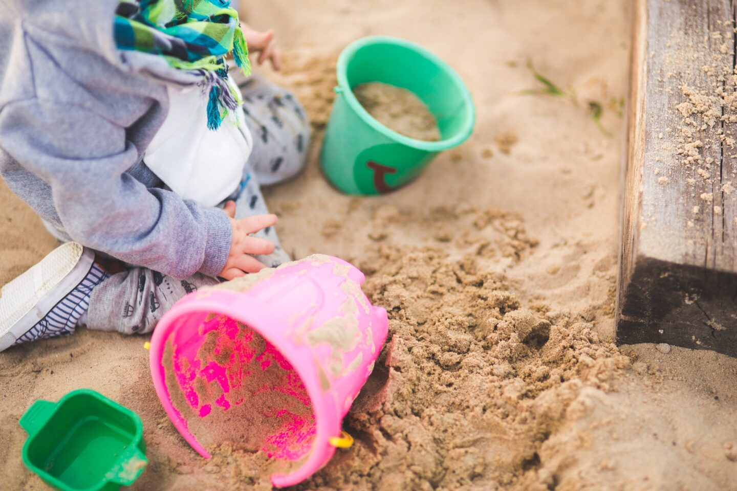playing in sandpit with buckets