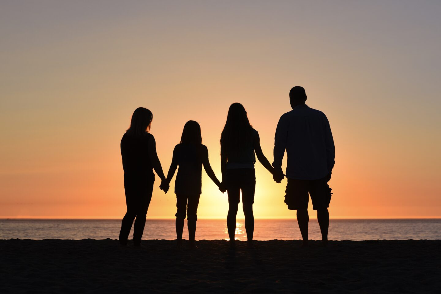 Family watching sunset on the beach