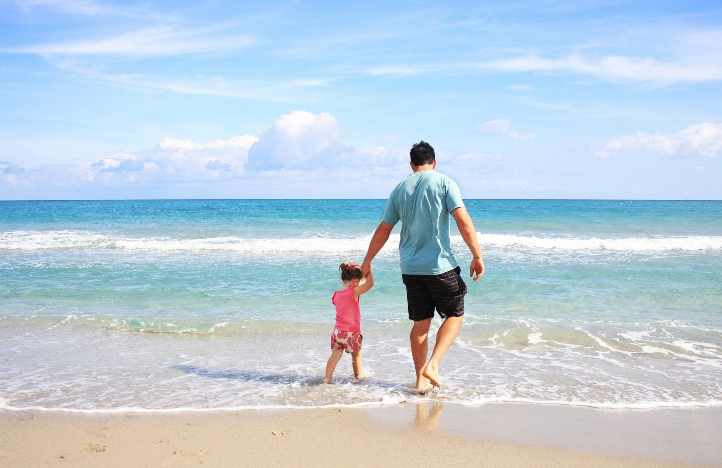 Daughter and Father paddling in water