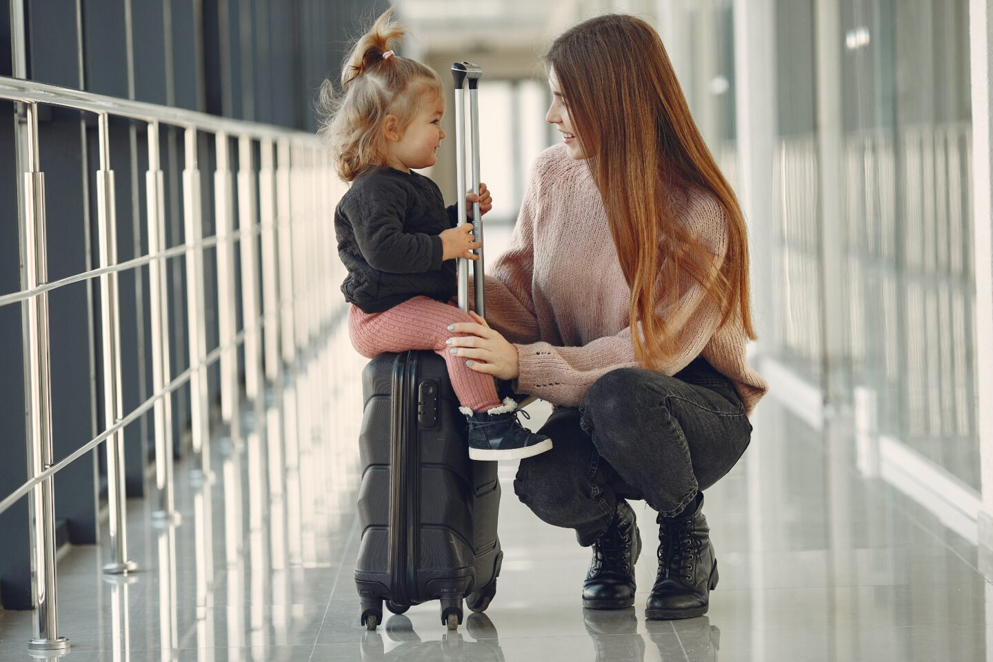 Mum and daughter with suitcase at airport