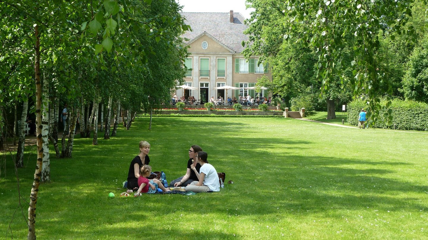 Family having picnic by large house