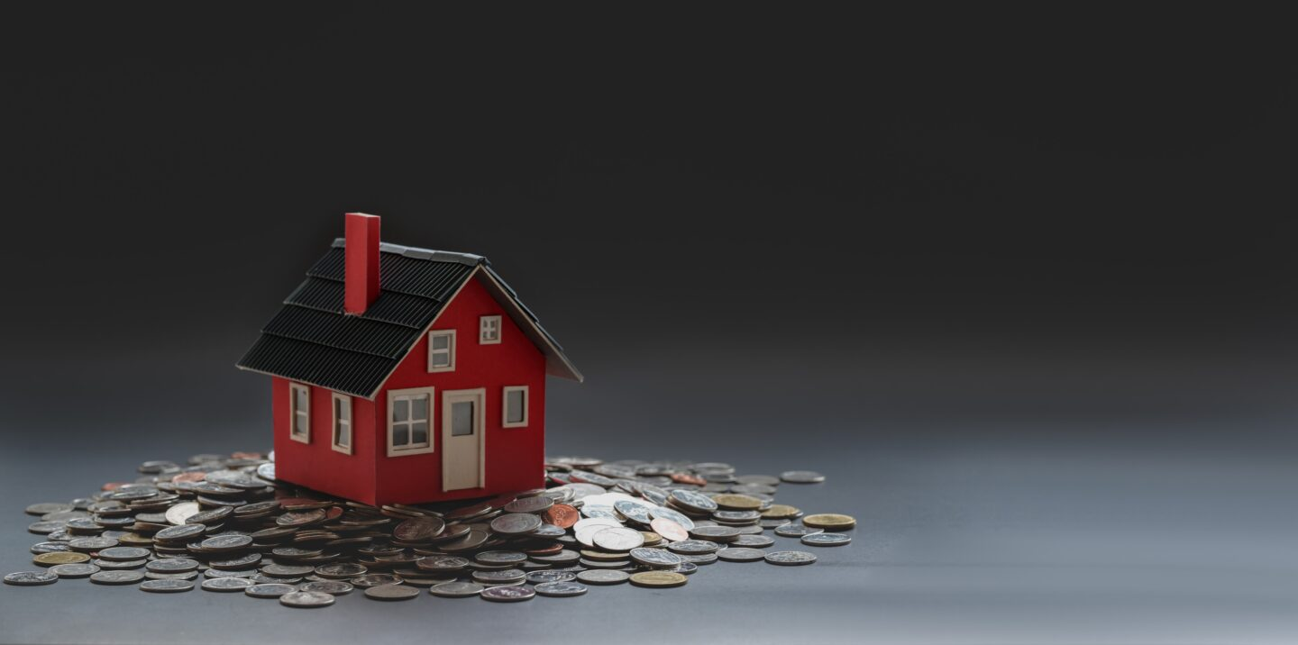Toy house surrounded with money