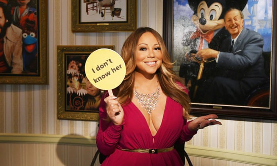 Mariah Carey holding an 'I don't know her' sign and smiling