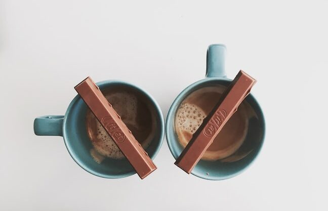 Two cups of coffee in blue mugs with Kit Kat bars resting over them
