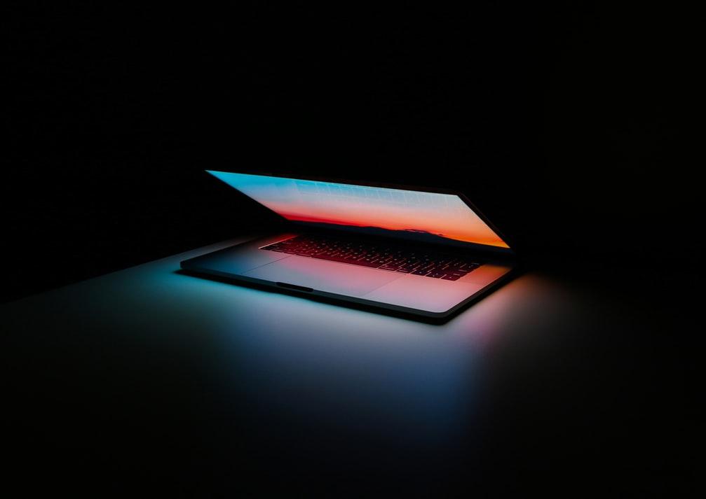 Half closed laptop in a dark room