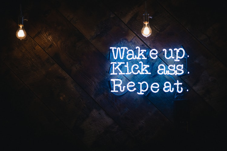 Neon blue sign saying 'wake up. Kick ass. Repeat'