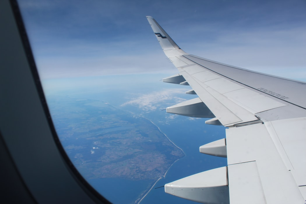 The view outside of an aeroplane window with blue skies and the wing of the aeroplane