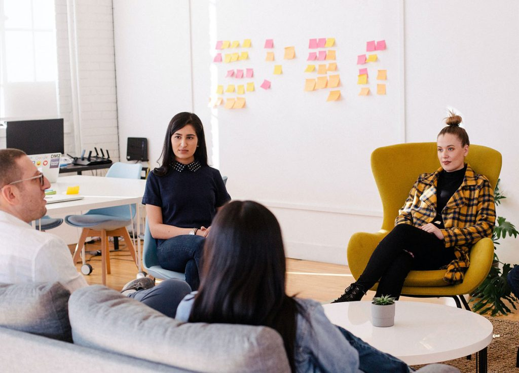 A group of employees in a team meeting in a clean, open office space