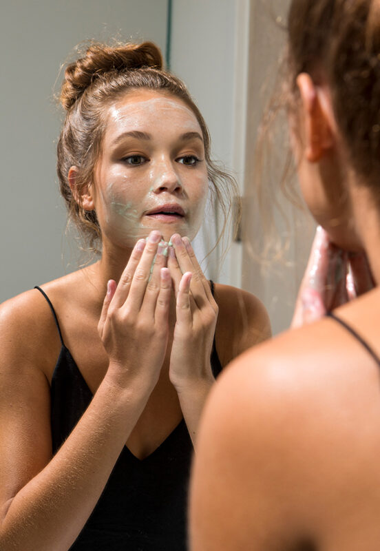 woman washing her face in front of the mirror
