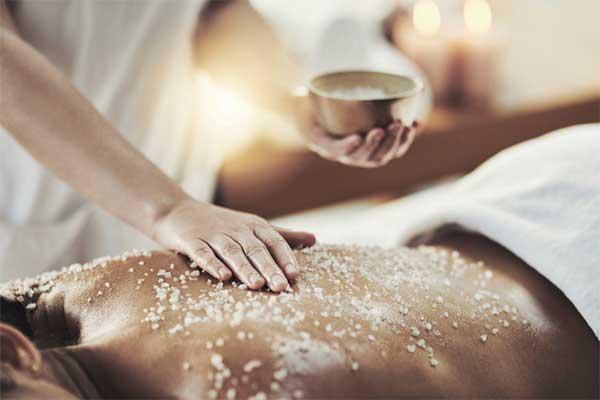 therapist applying a salt scrub to a woman's back
