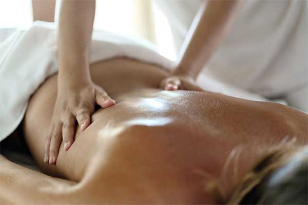 therapist applying massage techniques to a woman's back, during a Thai oil massage