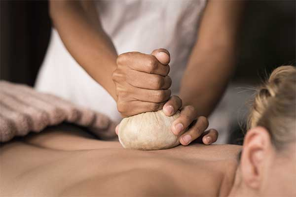 therapist using a Thai poultice on a woman's back