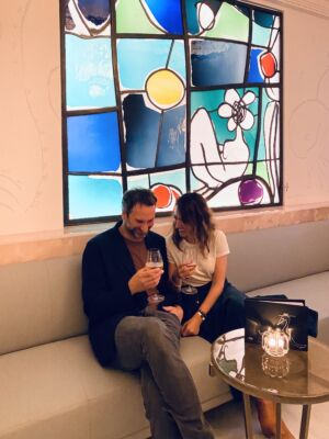 The Wick - Annie Morris and husband Idris Khan in The Painter's Room bar at Claridge's with her stained glass window (Courtesy of Annie Morris)