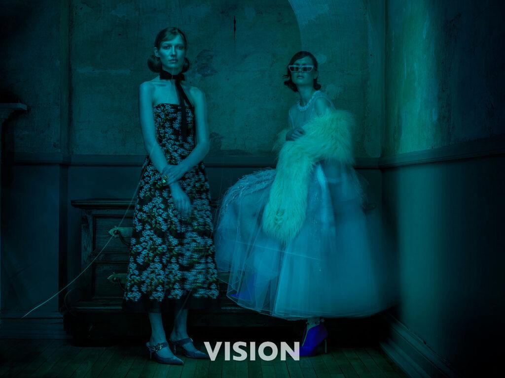 Two female models pose in big dresses, blue hue image
