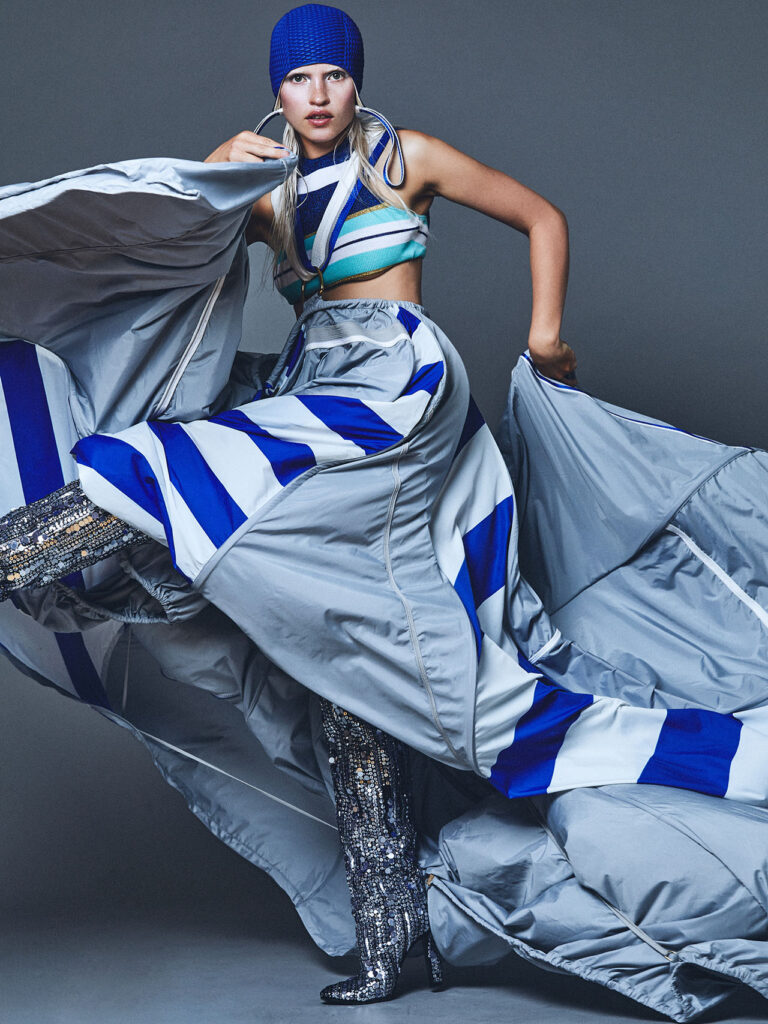 Woman dancing in big blue and grey dress for wonderland magazine
