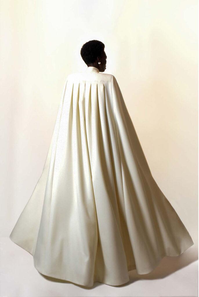 Woman models long white cloak dress