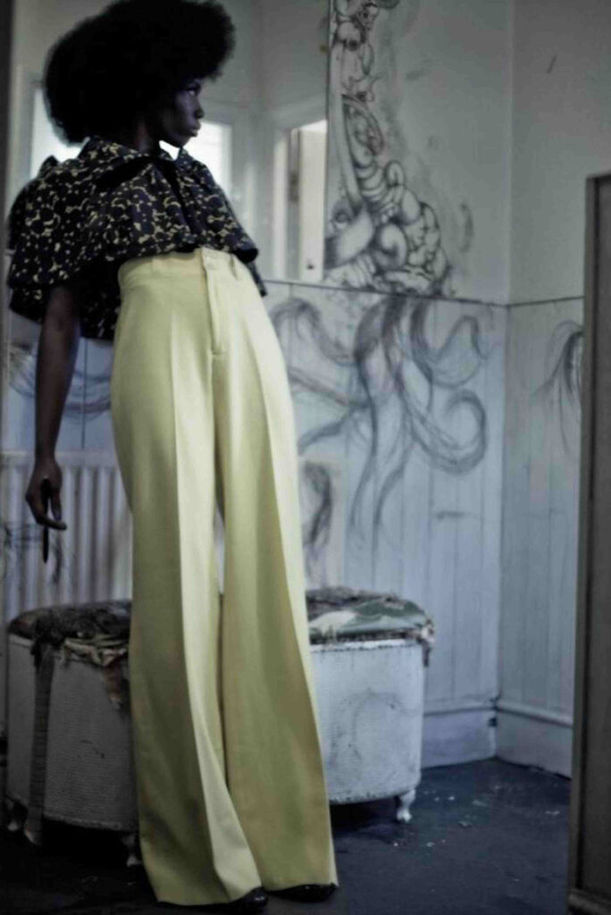 model poses with afro and yellow trousers