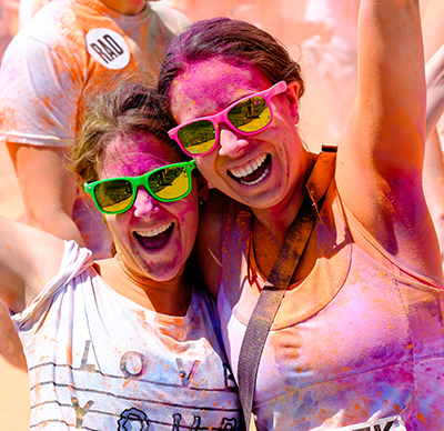 Toronto, Ontario, Canada - May 31, 2014: Two Female runners splattered with colourful powder smiling and cheering at the the Color Me Rad 5K Color Run on May 31, 2014 in Toronto, Ontario Canada.