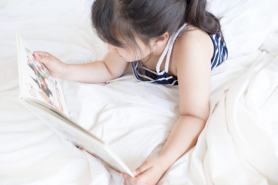 toy rotation system encouraging reading, little girl in bed reading a book