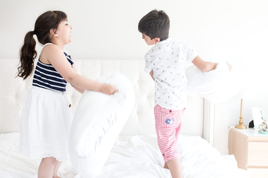 two kids having a pillow fight on a white bed. toy rotation system encouraging play.