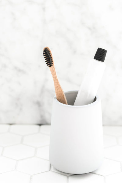banish visual clutter in the bathroom, toothpaste in a plain tube with bamboo toothbrush