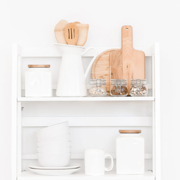 kitchen utensils stored in plan white containers with white cups and plates