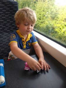 Small boy playing with toys on a train