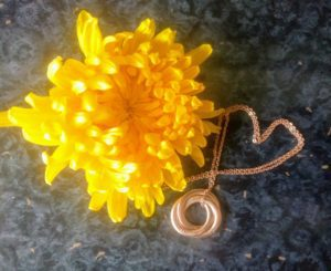 Personalised Rose Gold Necklace next to a yellow flower