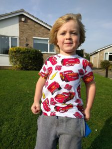 Boy in garden wearing Cars top
