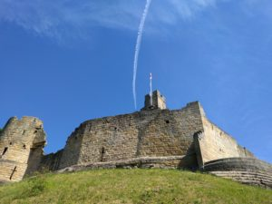 Prudhoe Castle looking up at castle walls with blue skies