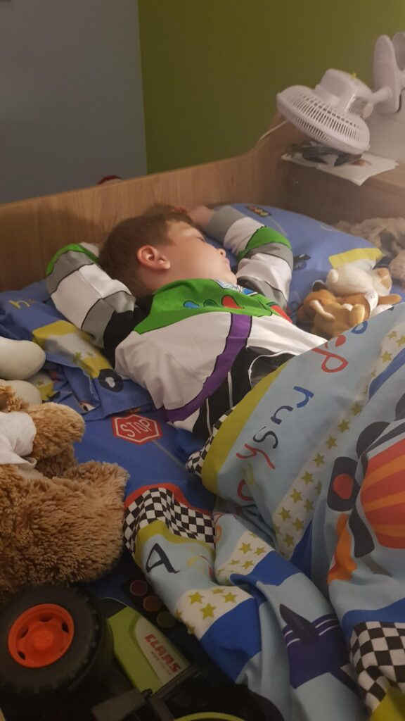 Sleeping boy is Buzz Lightyear PJs