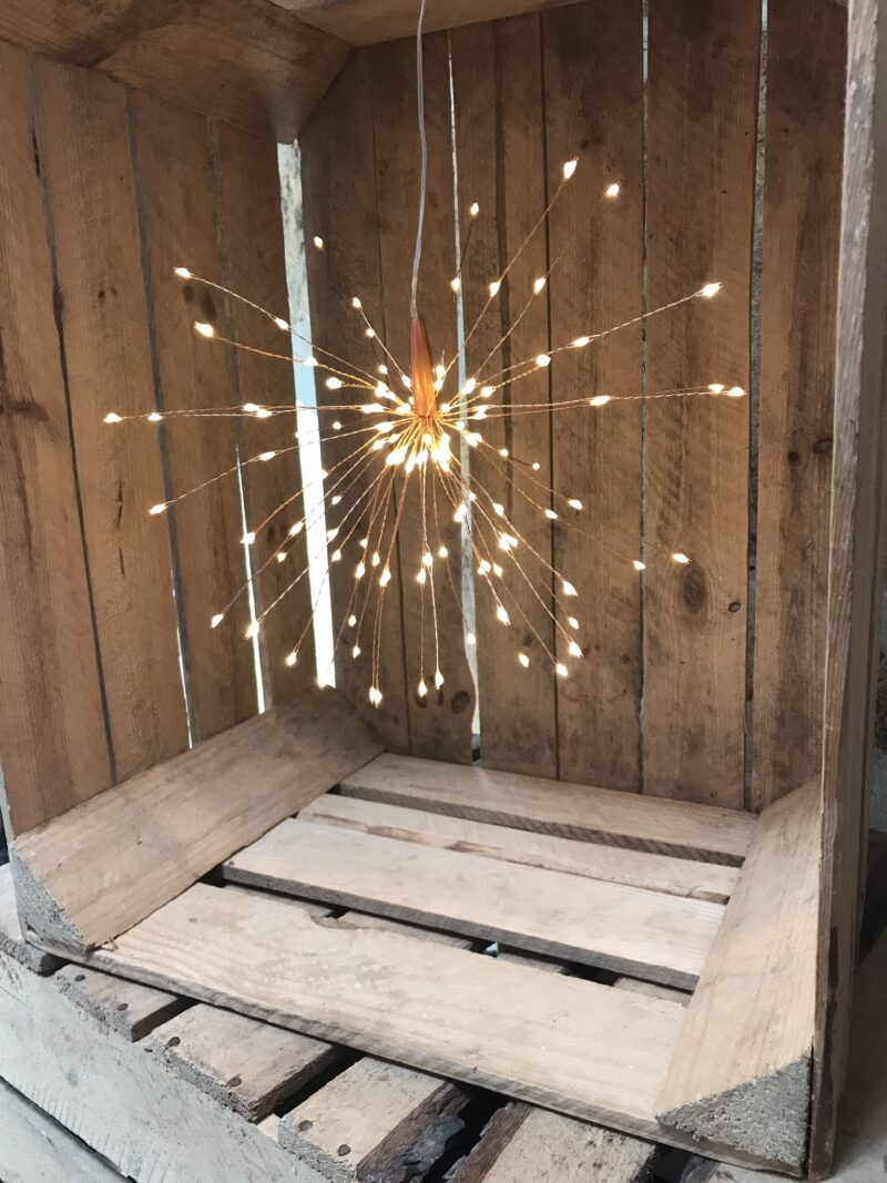 small hanging starburst light in a crate
