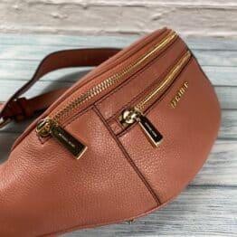 Michael Kors Mott Waist Bag in sunset peach sold by coopers closet