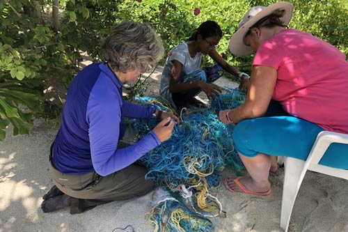 Expedition volunteers sorting recovered ghost nets, Maldives
