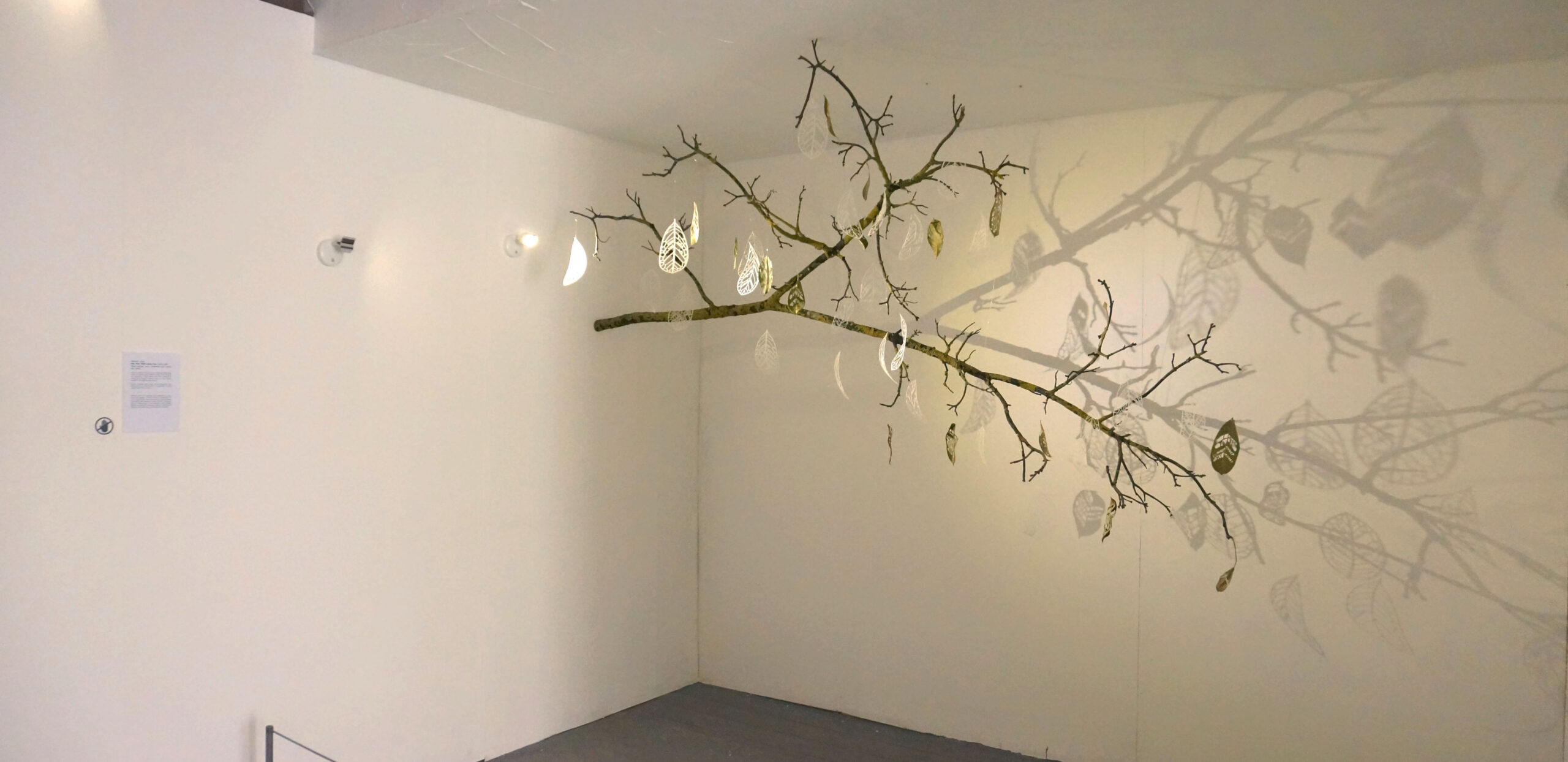 A mixed-media art installation made of carved leaves, glass leaves and a tree branch