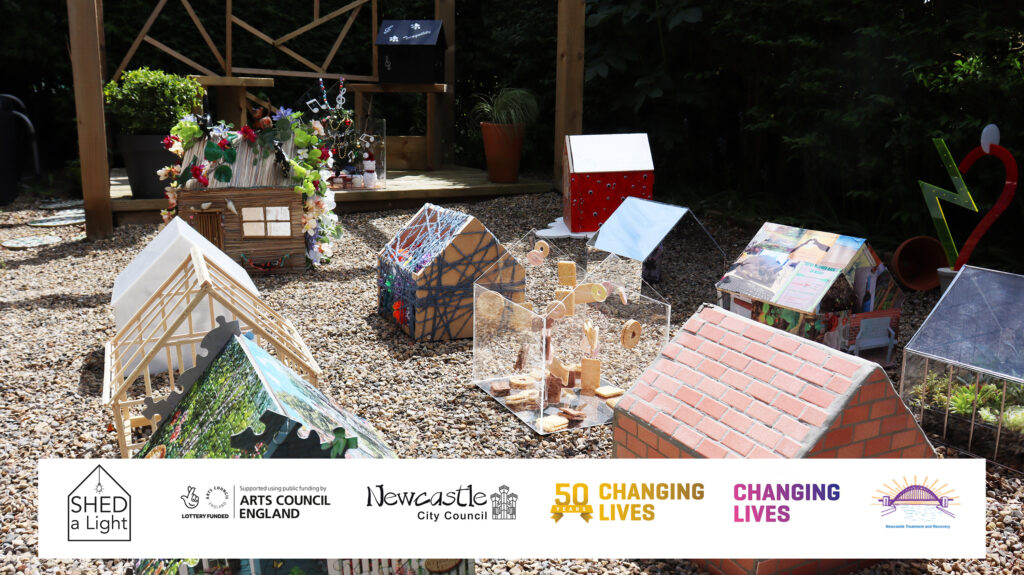This is a colour photograph of a garden scene with a gravel floor and hedge surrounding it. In the garden are twelve miniature sheds with a range of artistic designs. In the back of the frame, two of the sheds are sat on a covered wooden decking. Overlaying the image at the bottom is a banner containing six logos.